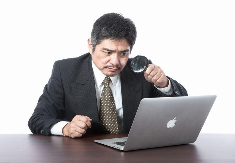 虫眼鏡でMacを見る男性